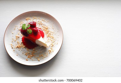 closeup top view of strawberry cheesecake with mint leaves on white plate and white table