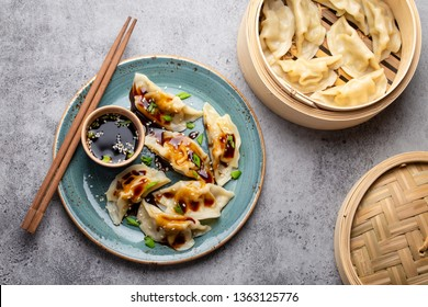 Close-up, top view of traditional Asian/Chinese dumplings in blue plate with soy sauce, chopsticks and a bamboo steamer on gray rustic stone background. Authentic Chinese cuisine