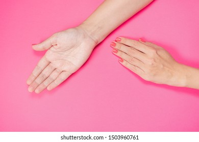 Closeup top view of two female beautiful hands. Empty opened palm isolated on pink background. Horizontal color photography.