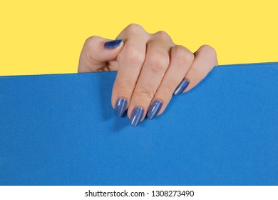Closeup top view of white female hand with shiny glossy modern blue gel polish. Macro of manicured nails of adult woman isolated on yellow and blue background. Horizontal color photography.