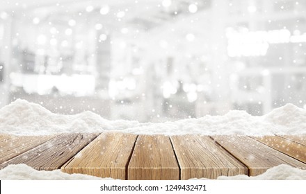 Closeup top wood table with Blur Background and snow christmas time, for your photo montage or product display, Wood table top on blur Christmas tree in snow, Space for placing items on the table.