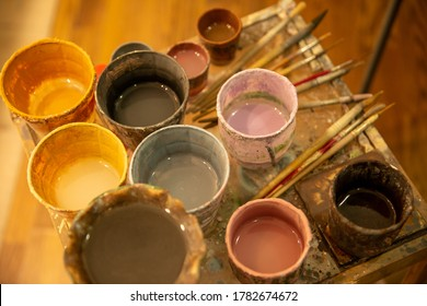 Close-up top-down view of pots of glaze and brushes at ceramic studio, Ragusa Ibla, Sicily.