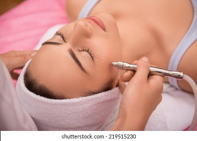 Close-up top-view side-view portrait of a young woman with a towel on her head lying on a table with closed eyes getting a laser skin treatment in healthy beauty spa salon