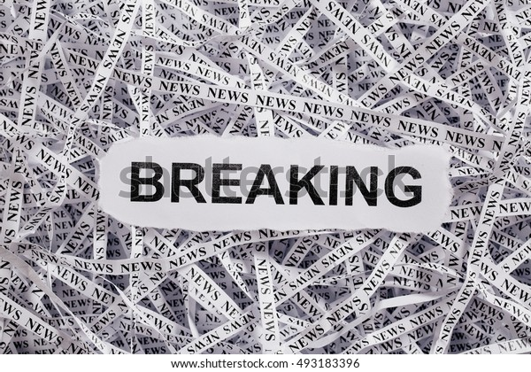Closeup torn pieces and tapes of paper with the word BREAKING. Black and White image. Concepts of money and business.