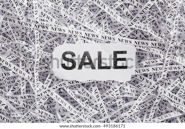 Closeup torn pieces and tapes of paper with the word SALE. Black and White image. Concepts of money and business.