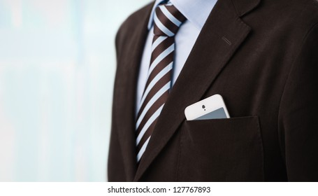 Closeup of torso of confident business man wearing elegant suit and mobile phone at pocket