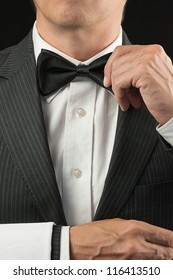 Close-up torso shot of a fine dining waiter in a bowtie and tux adjusting his bowtie with a white pressed napkin over his arm.