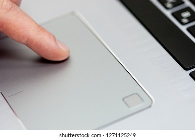 Closeup touchpad laptop with finger. finger on the touchpad. working at a laptop