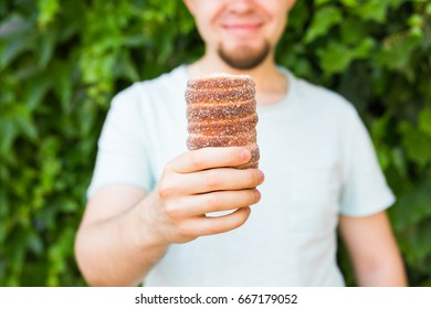 Close-up of tourist holds in hand Trdlo or Trdelnik background. Fresh Appetizing Trdlo or Trdelnik - Traditional National Czech Sweet Pastry Dough.