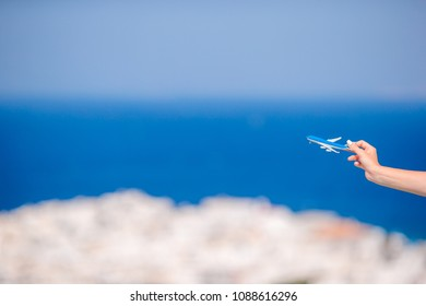 Closeup toy airplane in hands background the old greek village and blue sea