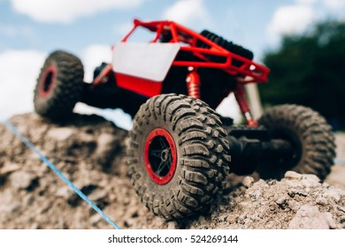 Close-up of toy crawler riding through rocks. Rc car roading on mountain landscape, handmade rally. Racing, extreme, entertainment, competitions concept