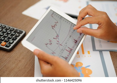 Closeup of trader working with candlestick chart and using tablet. Papers and calculator lying on desk. Trading and FOREX concept. Cropped view.