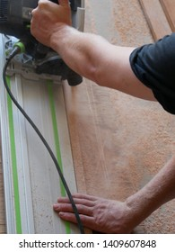 Closeup of a tradesman's hands and arms as he cuts a piece of timber with a power tool circular saw, cutting straight along a metal rail on a wooden cutting board spraying saw dust in Australia