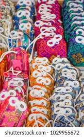 A closeup of traditional, colorful orange, blue, and pink lucky Shinto charms called 'omamori' which are popular in Japan and found at Shinto shrines.