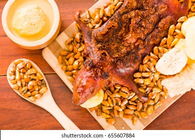 Closeup traditional ecuadorian dish, grilled guinea pig spread out onto wooden board, tostados and salsa on the side, seen from above
