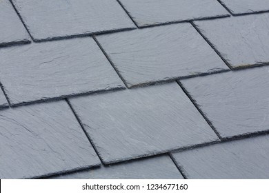 Closeup of traditional grey slate roof tiles on a pitched roof
