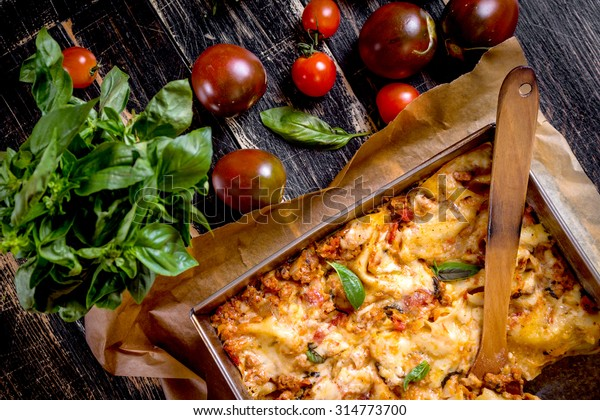Close-up of a traditional italian lasagna made with minced beef bolognese sauce topped with basil leafs served on a rustic dark wooden table