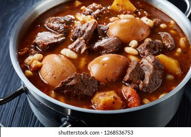 close-up of Traditional Jewish Cholent Hamin - main dish for the Shabbat meal, slow cooked beef with potato, beans and brown eggs in a pot on a black wooden table, vertical view from above