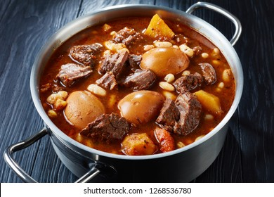 close-up of Traditional Jewish Cholent (Hamin) - main dish for the Shabbat meal slow cooked beef with potato, beans and brown eggs in a metal casserole on a black wooden table