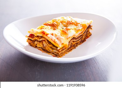 Close-up of a traditional lasagna made with minced beef bolognese sauce topped with basil leafs served on a white plate. Portion of succulent ground beef lasagne topped with melted cheese and garnishe