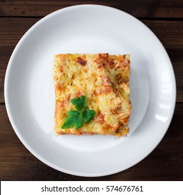 Close-up of a traditional lasagna topped with parskey leafs served on a white plate on dark wooden table. vertical