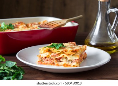 Close-up of a traditional lasagna topped with parskey leafs served on a white plate on dark wooden table