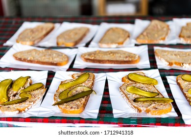 Closeup of traditional Polish food dish with sandwich of sliced pickles, lard and toasted bread slice at Warsaw Poland christmas market