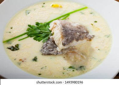Closeup of traditional Scottish soup Cullen skink with smoked haddock, potatoes and onions garnished with greens in white plate