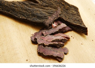 A closeup of traditional south african biltong on a wooden chopping board