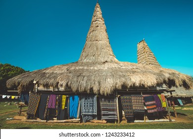 Close-up traditional straw roof house. Sumba village. Indonesia. The ethnic Sumbanese hut on the blue sky background. Authentic handmade carpets hanging next to the house. Local village.
