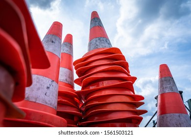 Closeup of traffic cones in front of blue cloudy sky
