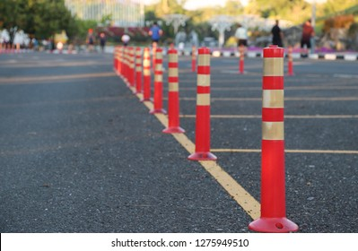 Closeup of traffic regulation pole and rumble strip on asphalt road in public park with people exercise background in the evening of sunny day. The symbol of safety first.