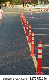 Closeup of traffic regulation pole and rumble strip on asphalt road in public park with people exercise background in the evening of sunny day. The symbol of safety first. Vertical view.