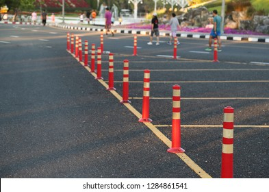 Closeup of traffic regulation pole and rumble strip on asphalt road in public park with people exercise background in the evening of sunny day. The symbol of safety transportation.