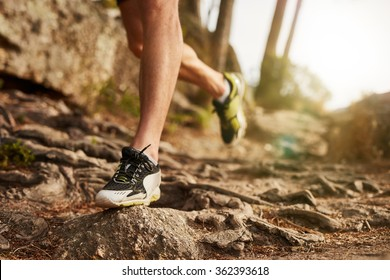 Close-up of trail running shoe on challenging rocky terrain. Male runner's legs working out on extreme terrain outdoors.
