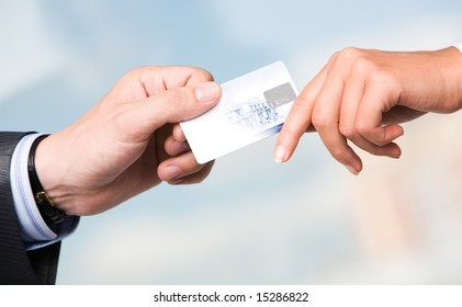 Close-up of transfer of credit card from maleâ??s hand to that of female over blue background