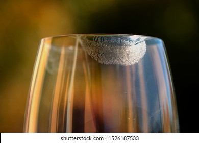 close-up of transparent lipstick imprints on wine glass in front of pastel colored background, transparent lipstick imprints on glass