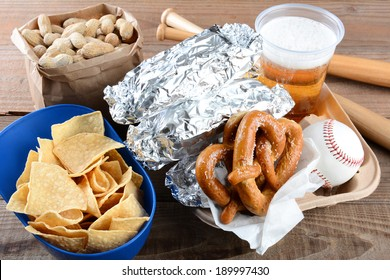 Closeup of a tray of food and souvenirs that one would find at a baseball game. Items include, hot dogs wrapped in foil, beer, peanuts, chips, baseball, mini bats and pretzels. Horizontal format.