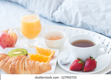 Close-up of tray with tasty breakfast on a bed.