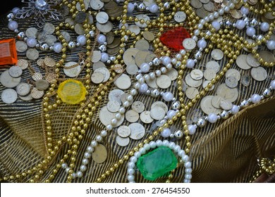Closeup of a treasure with coins, jewels and chains.