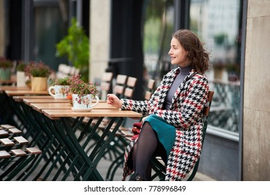 Close-up trendy autumn outfit of young sensual woman in a cafe on the street of Budapest. On the table are flowers in pots and lies a pumpkin. Europe vacation. Street style