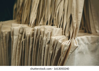 Close-up of a lot of trendy eco-friendly canvas bags hanging in a row.