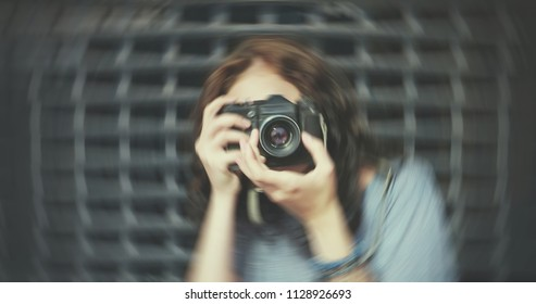 Close-up of trendy girl with vintage camera and background swirling about