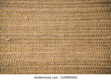 Closeup of a trendy straw wallpaper of ethnic style. Woven pattern background with bamboo and grass.