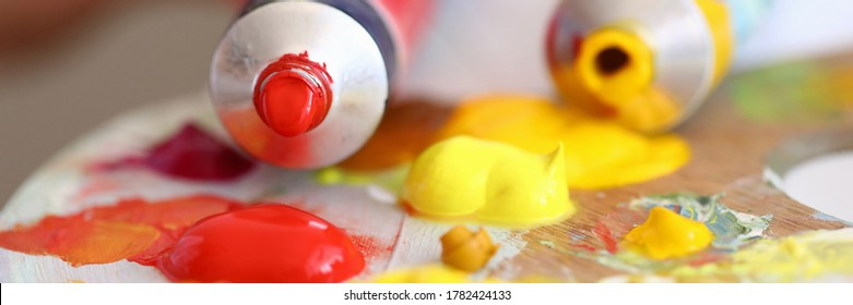 Close-up of tubes with red and yellow oil paints pouring on palette. Creamy texture. Tools for painting picture. Hobby and creative process. Art and artistry concept