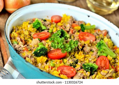 Close-up of tuna risotto with vegetables, tomatoes, broccoli and parsley in the old pan, onions, cans and oil in the background