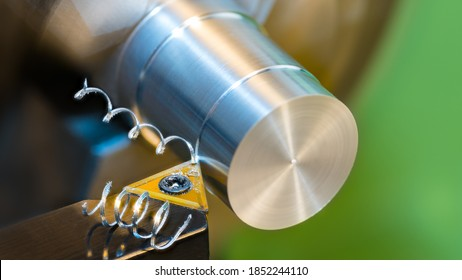 Closeup of turning cylindrical workpiece of aluminum alloy on a lathe machine. Black cutting tool bit with yellow triangular carbide insert and two beautiful spiral curled metal swarf. Chip machining.