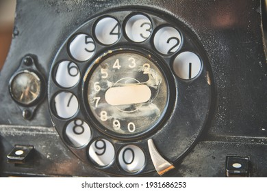 Close-up of turning wheel of old-fashioned vintage rotary phone. Retro technology