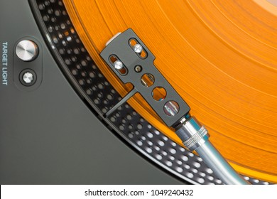 Closeup of turntable with orange vinyl record, top view