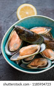 Close-up of a turquoise bowl with fresh uncooked green mussels, vertical shot